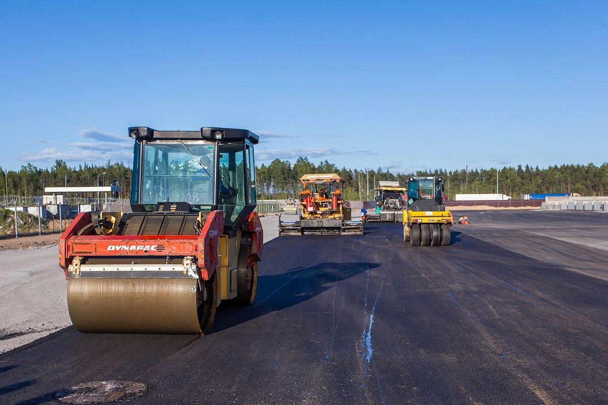 Укладка асфальта. Строительство дороги. Строительная фото съемка.