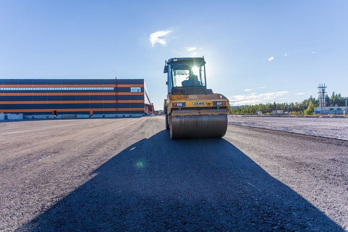 Укладка асфальта при строительстве дороги. Строительное фото.